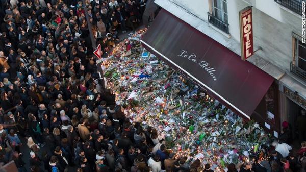 Hàng ngàn người đến thắp nến và đặt vòng hoa trước cửa nhà hàng Carillon nơi xảy ra một trong những vụ xả súng dã man của IS tại Paris đêm 13/11.