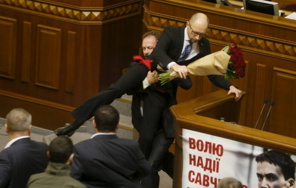 Rada deputy Oleg Barna removes Prime Minister Arseny Yatseniuk from the tribune, after presenting him a bouquet of roses, during the parliament session in Kiev, Ukraine, December 11, 2015. REUTERS/Valentyn Ogirenko