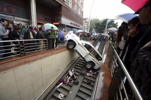 People look on as a car is stuck after falling into a stairs of an underpass, in Fuzhou, Fujian province, China, December 9, 2015. The driver, surnamed Yang, in her 30s, backed the car into the underpass entrance on Wednesday by mistaking the accelerator as the brake. No one was injured during the accident, local media reported. Picture taken December 9, 2015. REUTERS/Stringer