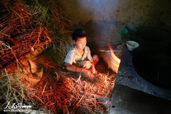 """Cậu bé Xiao Nan tại Hà Nam đang nhóm lửa nấu cơm. Mẹ em đã bỏ nhà đi làm trên thành phố được 5 năm. Cha em chỉ về thăm đúng 1 lần khi ông nội qua đời. Khi được hỏi em có nhớ cha mẹ không, em chỉ nói """"Không""""."""