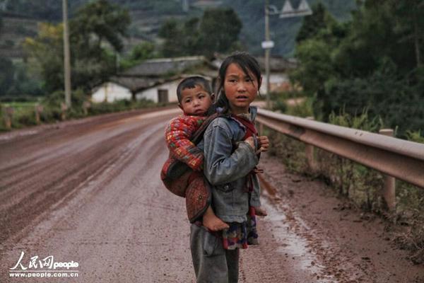 Qubi Wuluo địu em đi lang thang trên con đường ngập bùn trong khi các bạn cùng trang lứa đang ngồi trong lớp học.