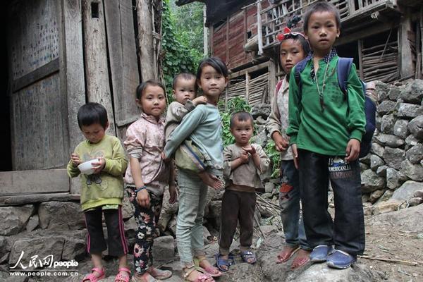 """Meng Xiaohua đi học về là phải tranh thủ trông em. Cô bé có đến 4 đứa em nheo nhóc bám lấy chị gái cũng chẳng """"to lớn"""" là bao."""