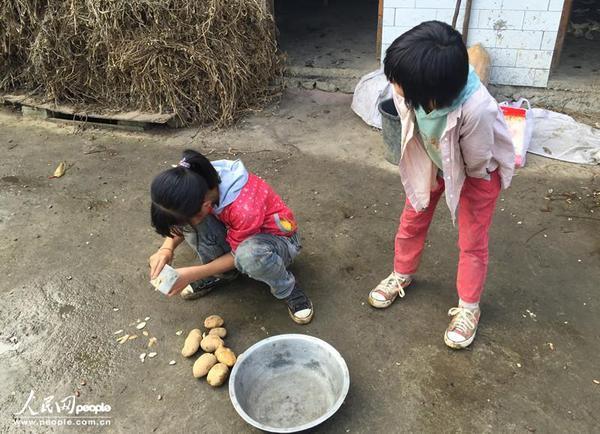 Hai chị em cô bé này đang gọt khoai nấu bữa tối. Các em hiện đang sống tại làng Baihua, tỉnh Quý Châu. Mẹ em đã chết vì bạo bệnh, còn cha thì lên thành phố kiếm tiền. Chỉ có hai chị em nương tựa vào nhau mà sống.