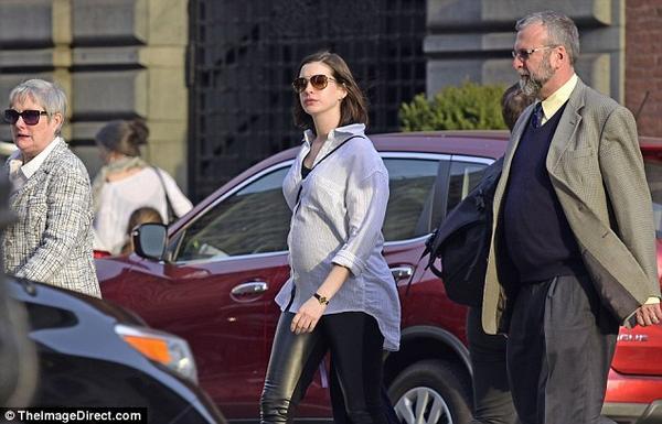 Cuối tuần qua, cánh săn ảnh của Daily Mail trông thấy Anne Hathaway và bố mẹ cô là ông bà Gerald - Kate Hathaway đi bộ trong khu trung tâm ở New York. Nữ diễn viên 33 tuổi mặc áo sơ mi lộ bụng bầu 5 tháng, gương mặt mộc tươi tắn. Sau 3 năm kết hôn, Anne và ông xã  Adam Schulman đang chờ đợi đứa con đầu lòng.