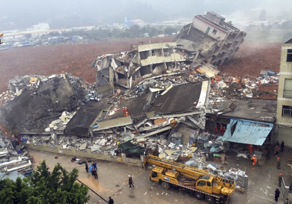 Rescuers search for survivors amongst collapsed buildings after a landslide in Shenzhen, in south China's Guangdong province, Sunday Dec. 20, 2015.  The landslide collapsed and buried buildings at and around an industrial park in the southern Chinese city of Shenzhen on Sunday authorities reported. (Chinatopix via AP) CHINA OUT