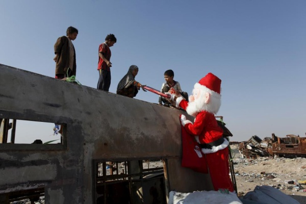 A volunteer wearing Santa Claus costume distributes presents to children at a poor community in Najaf, south of Baghdad, December 19, 2015. REUTERS/Alaa Al-Marjani