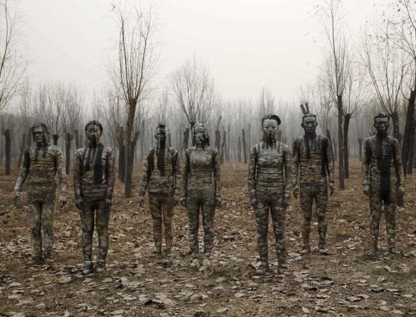 "Models painted in camouflage colors to blend in with the background pose for Chinese artist Liu Bolin's artwork ""Dongji"", or Winter Solstice, on the second day after China's capital Beijing issued its second ever ""red alert"" for air pollution, in Beijing, China, December 20, 2015. In this artwork, Liu wants to express his concerns about China and its people, including air pollution problem, Liu told Reuters. REUTERS/Kim Kyung-Hoon"