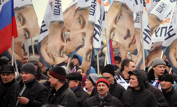 Supporters of Vladimir Putin carry portraits of him along the Moskva river
