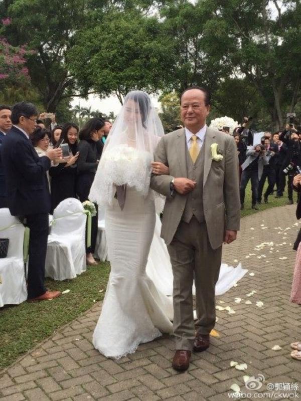 Cô được bố đưa vào lễ đường. Lễ cưới diễn ra đơn giản với tiệc ngoài trời.