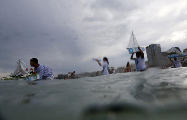 Các tín đồ của đạo Umbanda ở Brazil mang đồ lễ dâng thần biển Iemanja, tại bãi biển Rio de Janeiro. Nghi lễ này nhằm cảm ơn thần biển đã phù hộ cho họ trong một năm qua và cầu xin phước lành cho năm tới.