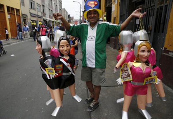 Một người Peru bán rong các hình nộm của Đệ nhất phu nhân nước này Nadine Heredia và Yahaira, một vũ công, bạn gái của cầu thủ bóng đá Jefferson Farfan, ở chợ Lima. Người dân Peru có truyền thống đốt hình nộm của những người nổi tiếng để tiễn biệt năm cũ và đón năm mới.