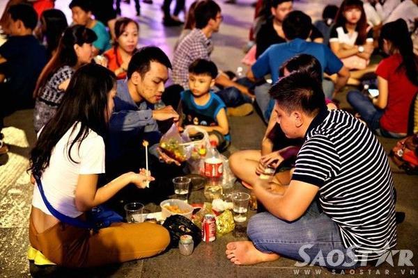 Nhiều người tranh thủ trải chiếu ngồi ăn uống để chờ xem pháo hoa.