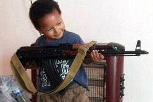 Cậu bé Isa năm 2014 đang cầm khẩu súng AK47, sau khi em cùng mẹ đến Syria, đầu quân cho IS.