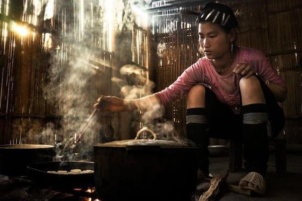 Một thiếu nữ dân tộc ở Sa Pa nấu cơm trong ánh nắng chiếu qua vách. König cho biết những món ăn ở đây rất ngon.