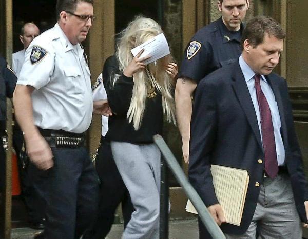 Ngôi sao trẻ một thời Amanda Bynes đầu tóc bù xù, cầm tờ báo che mặt khi bước ra từ tòa án hồi tháng 5/2013. Nữ diễn viên bị bắt vì tội danh ném ống tẩu hút ma tủy ra khỏi căn hộ ở tầng thứ 36 của một tòa nhà. Sau phiên tòa, Amanda bị đưa đến nhà giam.