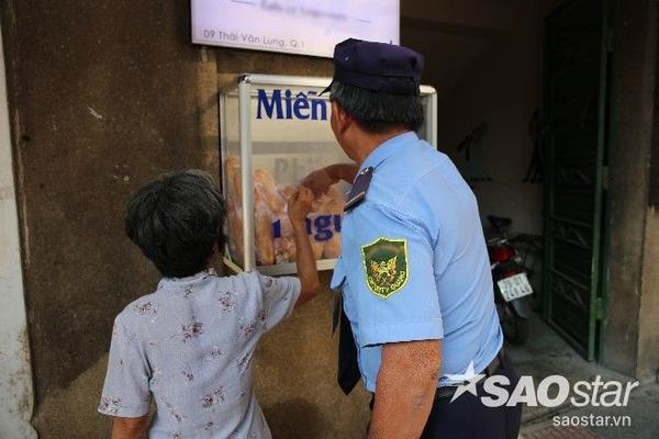 Chú bảo vệ ở tòa nhà gần đó lấy hộ gói bánh cho một cô bán hàng rong. Nhiều người dân nghèo cảm thấy ngại ngùng không dám tới nhận bánh.