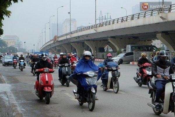 Trái ngược với thời tiết nắng ấm ở Sa Pa, từ sáng sớm nay, người Hà Nội ra đường trong tình trạng co ro trong thời tiết mưa rét. Ảnh: Định Nguyễn