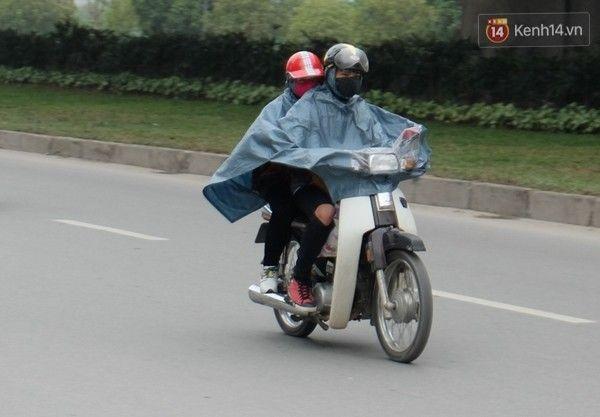 Những người dân đi làm sáng sớm phải khoác thêm áo mưa để chống chọi với cái lạnh. Ảnh: Định Nguyễn