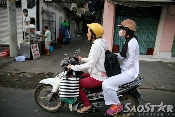 Cô nữ sinh được mẹ chở đi làm chủ quan không khoác thêm áo, phải giấu tay vào giữa hai chân cho bớt run.