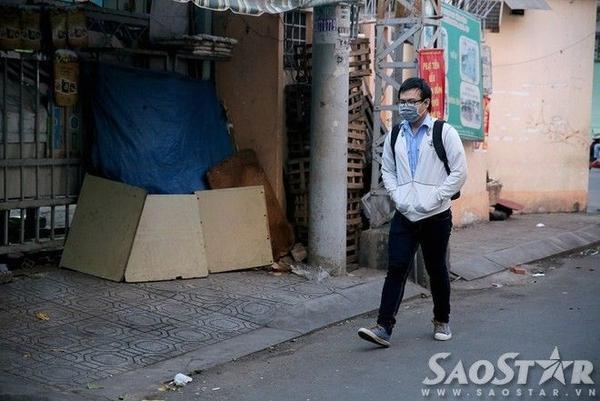 Một nam sinh viên đi bộ đến trường phải mặc áo khoác, đút tay vào túi vì lạnh.