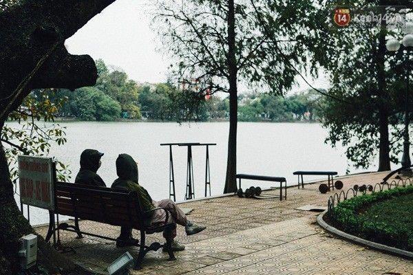 Hai người mặc kín bưng ngồi trò chuyện bên bờ Hồ.