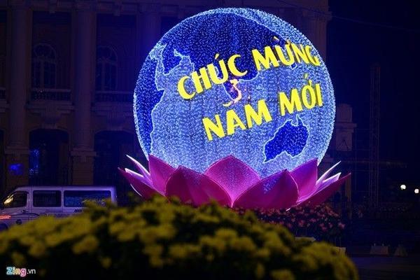 Biểu tượng trái đất trên đài sen trước cửa Nhà hát Lớn rực sáng về đêm.