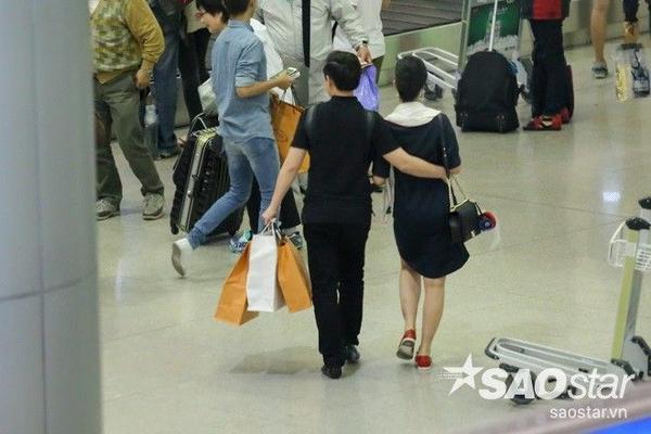 Cựu thành viên điển trai của nhóm Weboys không ngần ngại ôm eo bạn gái trong lúc đi lấy hành lý.