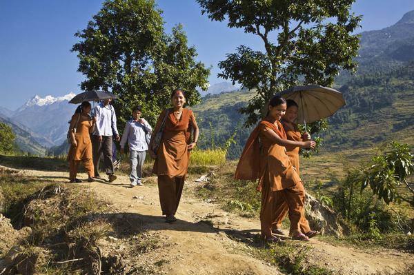 Các nữ sinh trong đống phục màu cam đang đi qua những ngọn đồi cao để tới trường ở Manaslu, Nepal.