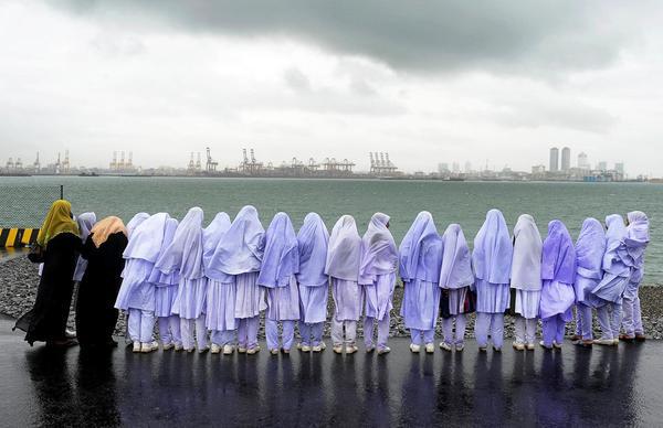 Các bé gái Hồi Giáo ở Sri Lanka đang đứng bên cạnh bờ biển ở Colombo sau chuyến đi từ làng Kalmunai cách đó 231 dặm (khoảng 371km). Tấm ảnh được chụp vào ngày 20/05/2013.