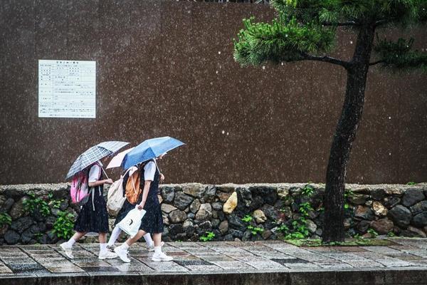 Các nữ sinh Nhật Bản đi đến trường dưới cơn mưa. Tấm ảnh được chụp ở Kyoto, tháng 6 năm 2013.
