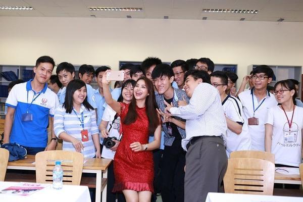 """Bộ đầm đỏ ren tưởng chừng như đơn giản nhưng lại giúp Phạm Hương khoe vóc dáng nuột nà với vòng eo đáng ngưỡng mộ. Hơn nữa, sắc đỏ khiến cô trở nên nổi bật hơn khi ở trong """"vòng vây"""" của các bạn sinh viên."""