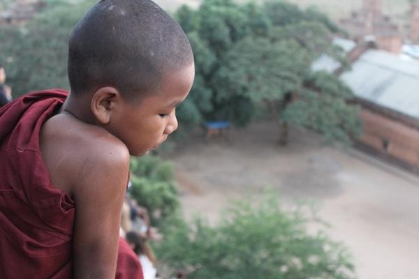 ... và một chú tiểu ngồi cùng vài du khách trên những bậc thang của chùa Shwe San Daw trong ánh mặt trời.