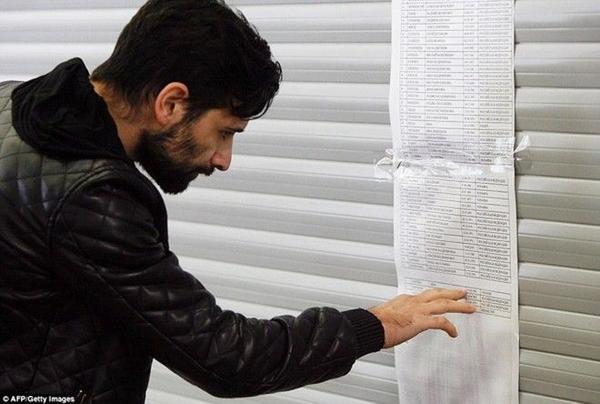 Một người đàn ông kiểm tra danh sách các hành khách trên chuyến bay gặp nạn.