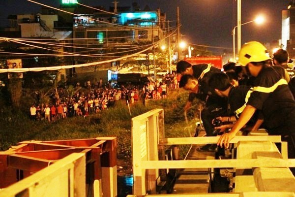Hàng trăm người dân hiếu kỳ đứng xem cảnh sát cứu hội.
