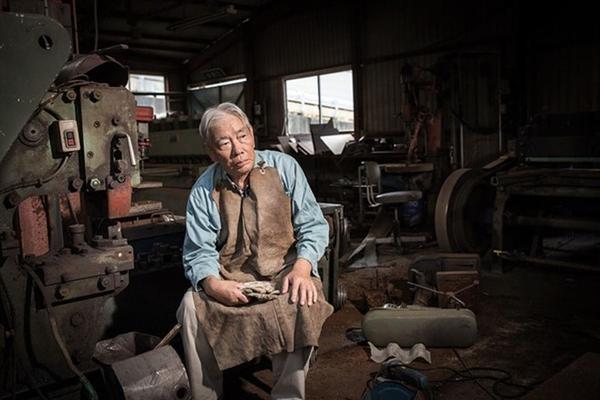 """Ông Katsuyuki Yashima đang ngồi trong khu xưởng của gia đình. Trước đây, gia đình ông có 15 nhân công, nhưng sau khi trận động đất sóng thần xảy ra, gia đình ông Katsuyuki cho biết họ sẽ không quay về Namie nữa dù cho thị trấn có được kiến thiết và mở cửa trở lại. """"Tôi sẽ không quay về vì tôi không thể kinh doanh được nữa. 10 năm nữa, Namie sẽ trở thành thị trấn ma. Theo khảo sát, chỉ có 20% người dân muốn quay trở lại. Năm tháng trôi qua, mọi người đã và đang xây dựng cuộc sống, sự nghiệp ở một vùng đất mới, để rồi cuối cùng, sẽ chẳng ai quay lại nữa cả"""", ông Katsuyuki (hiện đang sống ở thành phố Iwaki) cho biết."""