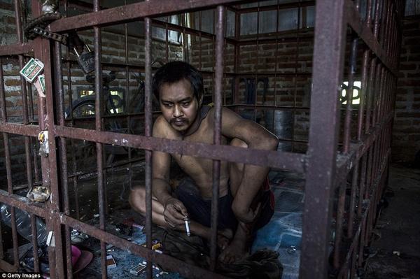 Suhananto, 30 tuổi, ngồi bên trong một cái lồng sắt