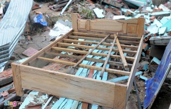 Giường cưới mới đóng dành cho đôi vợ chồng trẻ nằm chỏng chơ trên nền gạch đổ nát của căn nhà.