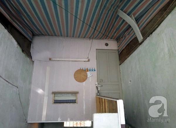 Một gia đình trên tầng 2 phải dùng bạt che chắn mưa và tránh bụi bẩn rơi xuống.