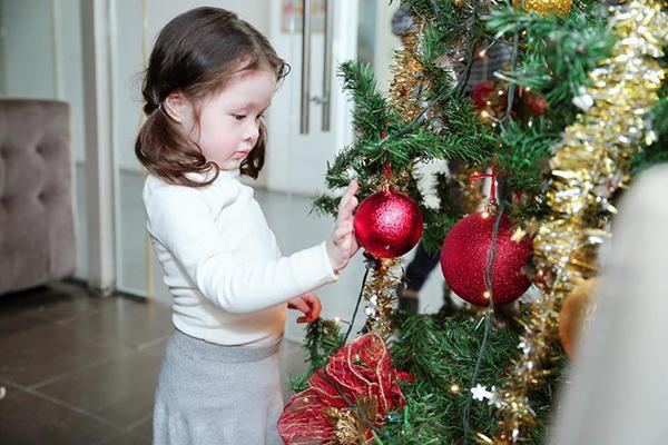 Bé Cadie Mộc Trà nhà Elly Trần thích thú trước những quả bóng sắc màu của cây thông Noel.