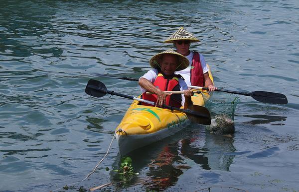 """Hai du khách người Mỹ hào hứng với """"chiến lợi phẩm"""" đầu tiên thu được là một túi nilon chứa đầy rác thải đang trôi bồng bềnh trên dòng nước."""