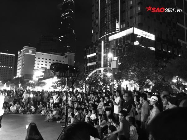 Mọi người tập trung khá đông trước sân khấu, chăm chú thưởng thức các tiết mục mà các nghệ sĩ trình diễn.