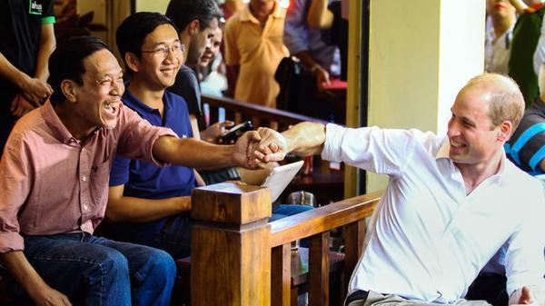 Hoàng tử Anh William bắt tay với một người dân Hà Nội tại quán cafe trên phố Thuốc Bắc. Ảnh: Tuổi Trẻ.