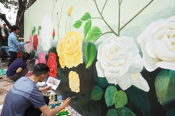 Lối vào khu diễn ra lễ hội hoa, nhân viên đang vẽ trang trí chủ đề của lễ hội hoa trên tường.