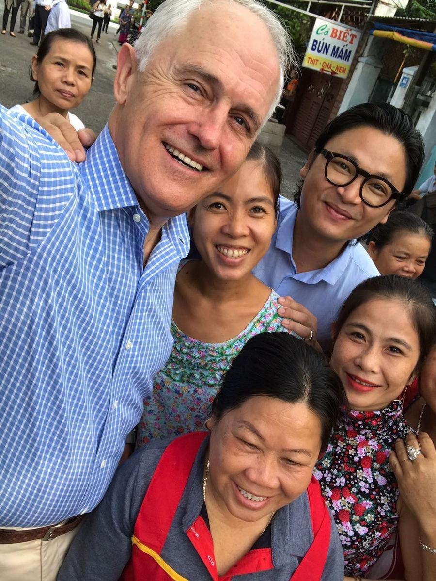 Ông Turnbull chụp ảnh selfie cùng cô bán bánh mì và người dân sống gần đó.